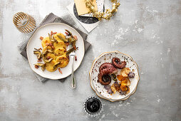Fried octopus with potato crips and ink mayonnaise, and baked semolina disks with artichokes and smoked bacon