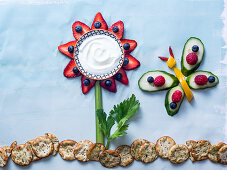 Creative flower and butterfly made of fruits and vegetables with berry petals, yogurt center and celery stalk