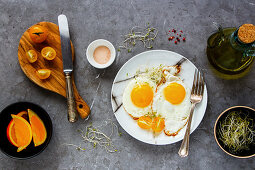 Breakfast with fried eggs, micro greens and tomatoes flat lay