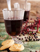 Elderberry mulled wine and cookies on a wooden surface