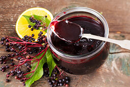 Homemade elderberry and orange jelly in a glass with a spoon