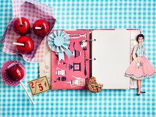 Paper doll and nostalgic recipe book on blue plaid