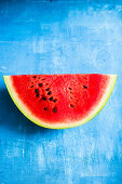 A slice of watermelon on a blue surface