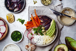 Fresh healthy vegetarian bowl for lunch with baked carrots and red onion, coucous and sliced avocado