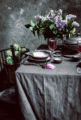Tablecloth setting with artichokes, flowers and red wine