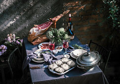 Tablecloth setting with artichokes, red wine and jam serrano leg.