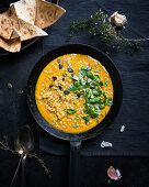 Yellow vegan lentil and pumpkin dhal with toasted unleavened bread (India)