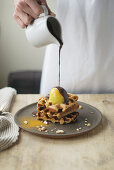 Woman pouring chocolate sauce on waffles