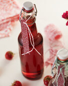 Homemade strawberry syrup in a flip-top bottle