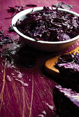 Sliced red cabbage in a bowl with some scattered on the table