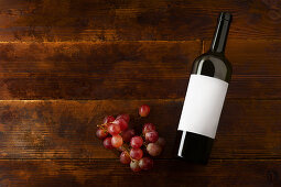 A wine bottle with a blank label and grapes