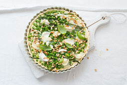 Unbaked pea tart with green beans, goat's cheese and pine nuts