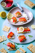 Crackers with cream cheese and lightly salted salmon, lemon and green onions