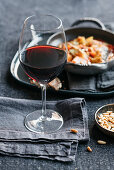 A glass of red wine with a bowl of pine nuts on a grey surface