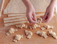 Tying raw dough strips into knots before frying