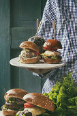 Man holding in hands homemade classic and mini burgers in wheat and black buns