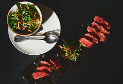 Slices of tasty meat and bowl with arugula and mushroom salad on black background