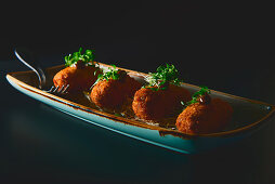 Bowl with set of yummy cutlets served with herbs on long ceramic plate on black background