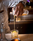 A bartender pouring a drink through a sieve into a cocktail glass