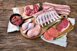 Various types of meat on wooden table