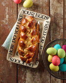 A glazed bread plait and coloured Easter eggs in a wire basket