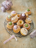 Mini Bundt cakes on a wire rack with coloured quail's eggs and Easter decorations