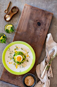 A boiled egg in a nest of herbs with lemon dressing, sesame seeds and cress