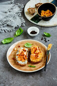 Close up of smoked salmon toasts on plate with soft goat cheese and basil over grey concrete table background