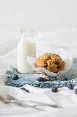 A blueberry muffin and a bottle of milk on a napkin on a bed