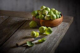 Brussels sprouts in a wooden bowl with a peeler
