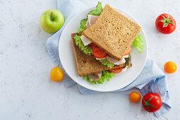 Sandwich mit Salat, Schinken, Tomate und Käse