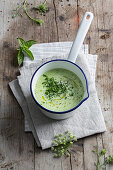 Cream of herb soup in a saucepan