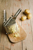 Boiled potatoes in a potato ricer on a wooden board