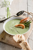 Green asparagus soup with prawns and baguette