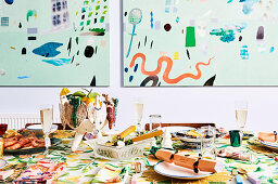 Colorfully laid Christmas table, abstract murals in the background
