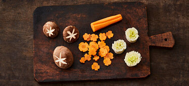 Vegetables and mushrooms being cut into decorative shapes