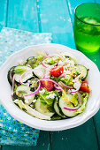 Summery cucumber salad with tomatoes and onions