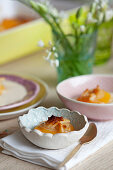 Baked apricots with almonds on vanilla ice cream
