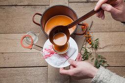 Pouring hot buckthorn jam into a mason jar