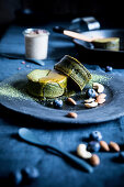 Matcha pancakes with honey, nuts, almonds and blueberries on a plate