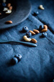 Blueberries, almonds and cashews on a blue tablecloth
