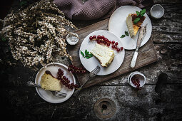 Cheese cake pieces served on plate with berry on dark wooden table