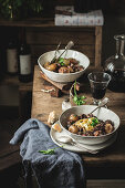 Traditional Boeuf Bourgingnon dish served with pasta side in bowls on wooden table