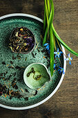 Kräutertee lose und aufgebrüht auf grüner Keramik