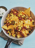 Nachos with minced meat, jalapenos and sweetcorn in a pan