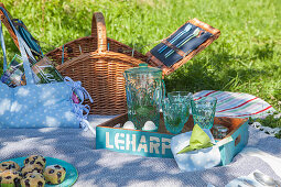 Jug, glasses and hand-sewn bag on picnic blanket