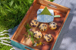 Hand-sewn serviette dispenser and muffins on wooden tray