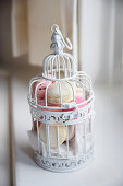 Various macaroons in a decorative bird cage