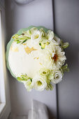A wedding cake decorated with gold leaf and white flowers