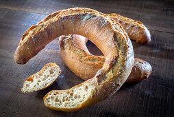 Two white U-shaped loaves, one sliced